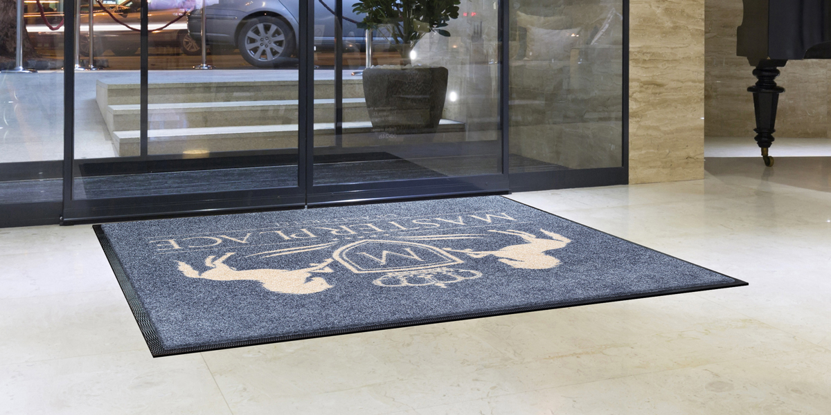 Jet-Print - grey Jet-Print mat with beige elements in front of the door of a hotel